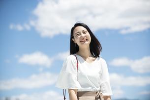 青空をバックに笑っている女性の写真素材 [FYI03436566]