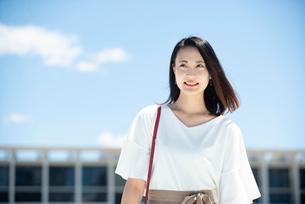 建物の前に立って笑っている女性の写真素材 [FYI03436702]