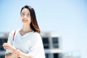建物の前に立って笑っている女性の写真素材 [FYI03436704]