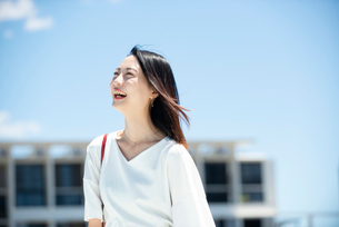 建物の前に立って笑っている女性の写真素材 [FYI03436705]