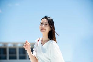 建物の前に立って笑っている女性の写真素材 [FYI03436706]
