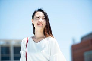 建物の前に立って笑っている女性の写真素材 [FYI03436794]