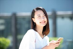 スマホを持って笑っている女性の写真素材 [FYI03436795]