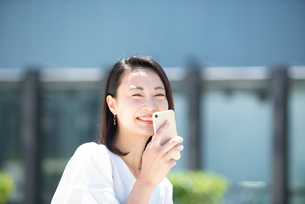 スマホを持って笑っている女性の写真素材 [FYI03436796]