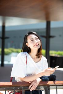 スマホを持って笑っている女性の写真素材 [FYI03436816]