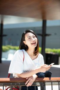 スマホを持って笑っている女性の写真素材 [FYI03436817]