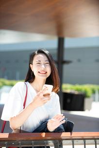 スマホを持って笑っている女性の写真素材 [FYI03436959]