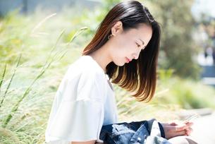スマホを持って笑っている女性の写真素材 [FYI03436968]