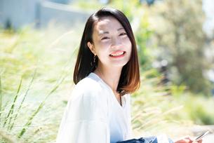 スマホを持って笑っている女性の写真素材 [FYI03436969]