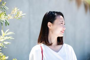 日差しを浴びながら笑っている女性の写真素材 [FYI03437009]