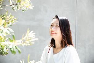 日差しを浴びながら笑っている女性の写真素材 [FYI03437522]