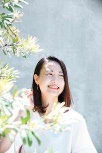 日差しを浴びながら笑っている女性の写真素材 [FYI03437526]