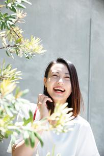 日差しを浴びながら笑っている女性の写真素材 [FYI03437527]