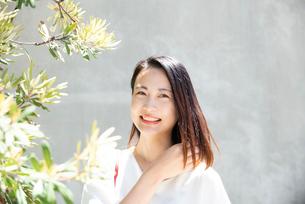 日差しを浴びながら笑っている女性の写真素材 [FYI03437530]