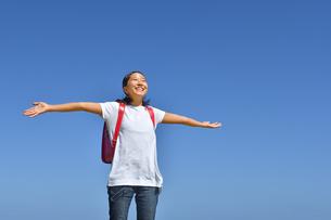 青空で手を広げる小学生の女の子(ランドセル)の写真素材 [FYI03437533]