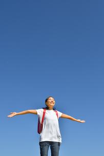 青空で手を広げる小学生の女の子(ランドセル)の写真素材 [FYI03437534]