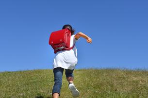青空で走る小学生の女の子(後姿)の写真素材 [FYI03438235]