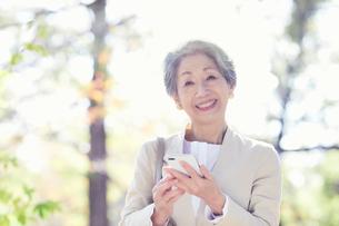 スマートフォンを持つシニア女性の写真素材 [FYI03438300]