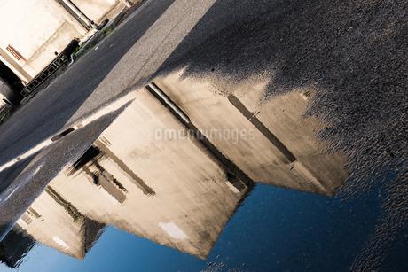 水溜りに反映した倉庫の写真素材 [FYI03438443]