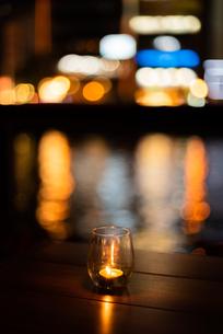 グラスキャンドルと夜の街の写真素材 [FYI03438461]
