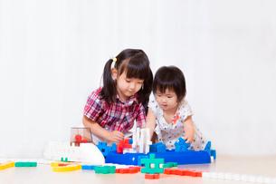ブロックで遊ぶ幼い女の子2人。遊び、姉妹、仲良し、知育イメージの写真素材 [FYI03439206]