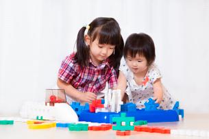 ブロックで遊ぶ幼い女の子2人。遊び、姉妹、仲良し、知育イメージの写真素材 [FYI03439207]
