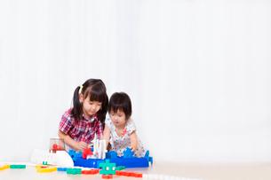 ブロックで遊ぶ幼い女の子2人。遊び、姉妹、仲良し、知育イメージの写真素材 [FYI03439208]