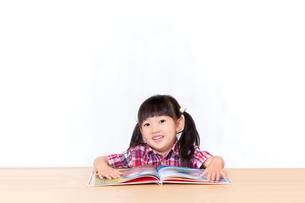 白背景の前で本を読む幼い女の子。幼児、教育、読書、学習、成長、育児イメージの写真素材 [FYI03439209]