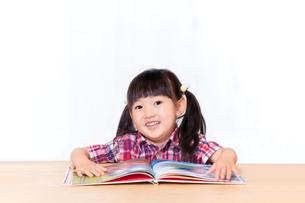 白背景の前で本を読む幼い女の子。幼児、教育、読書、学習、成長、育児イメージの写真素材 [FYI03439210]