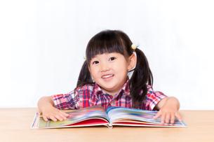 白背景の前で本を読む幼い女の子。幼児、教育、読書、学習、成長、育児イメージの写真素材 [FYI03439211]