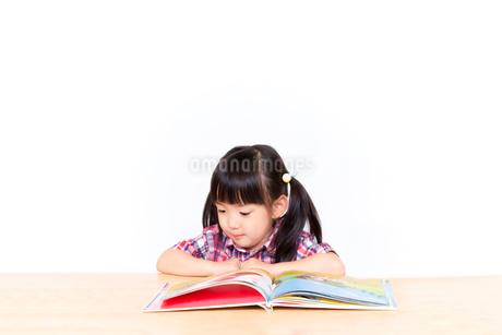 白背景の前で本を読む幼い女の子。幼児、教育、読書、学習、成長、育児イメージの写真素材 [FYI03439212]