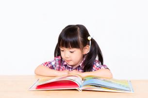 白背景の前で本を読む幼い女の子。幼児、教育、読書、学習、成長、育児イメージの写真素材 [FYI03439213]