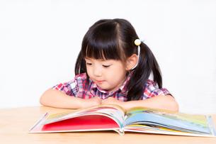 白背景の前で本を読む幼い女の子。幼児、教育、読書、学習、成長、育児イメージの写真素材 [FYI03439214]