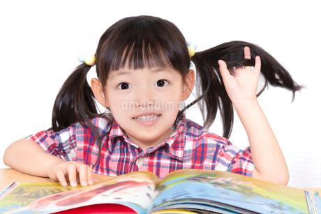 白背景の前で本を読む幼い女の子。幼児、教育、読書、学習、成長、育児イメージの写真素材 [FYI03439215]