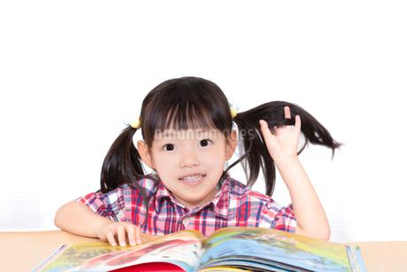 白背景の前で本を読む幼い女の子。幼児、教育、読書、学習、成長、育児イメージの写真素材 [FYI03439216]