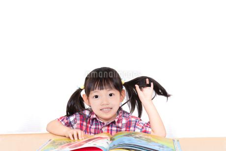 白背景の前で本を読む幼い女の子。幼児、教育、読書、学習、成長、育児イメージの写真素材 [FYI03439217]