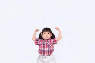 白背景でガッツポーズをする幼い女の子。積極的、前向き、元気イメージの写真素材 [FYI03439219]