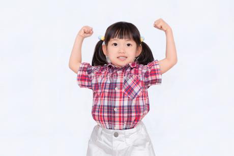 白背景でガッツポーズをする幼い女の子。積極的、前向き、元気イメージの写真素材 [FYI03439220]
