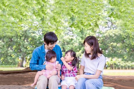 新緑の公園で遊ぶ家族4人。幸せ、愛情イメージの写真素材 [FYI03439225]