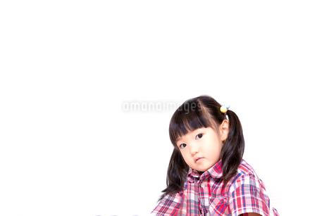 不信感の眼で見つめる幼い女の子。反抗、反発、孤立イメージの写真素材 [FYI03439226]