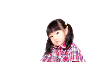 不信感の眼で見つめる幼い女の子。反抗、反発、孤立イメージの写真素材 [FYI03439227]