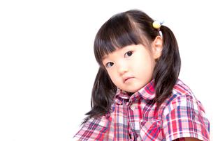 不信感の眼で見つめる幼い女の子。反抗、反発、孤立イメージの写真素材 [FYI03439228]