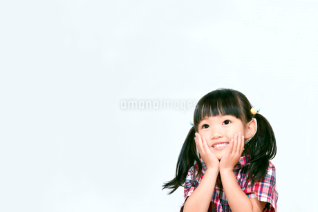 顎に両手を当てて遠くを見つめる幼い女の子。希望、夢、幸せ、楽しみイメージの写真素材 [FYI03439229]