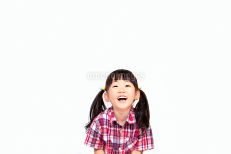 笑顔で上を見つめる幼い女の子。幸せ、希望、夢イメージの写真素材 [FYI03439230]