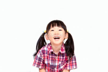 笑顔で上を見つめる幼い女の子。幸せ、希望、夢イメージの写真素材 [FYI03439231]