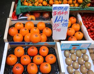 香港は九龍半島の旺角(モンコック/Mong Kok)の市場で売られるポルトガル産の富有柿。世界各国からの果物が香港では売られるの写真素材 [FYI03439439]