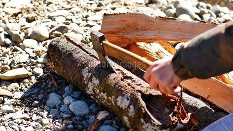 キャンプ場で斧を使って薪をわる日本人の手の写真素材 [FYI03441002]