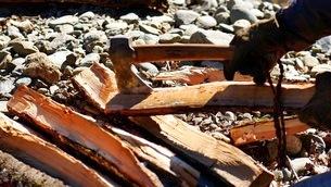 キャンプ場で薪を割る手袋の人の写真素材 [FYI03441003]