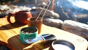 キャンプ場の道具と差し込む朝日の写真素材 [FYI03441005]