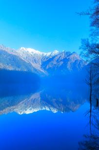 快晴の上高地 大正池に霧と冠雪の穂高連峰に紅葉の写真素材 [FYI03441367]